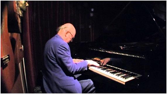 hugo van Neck achter de piano op ruiterstraat 14